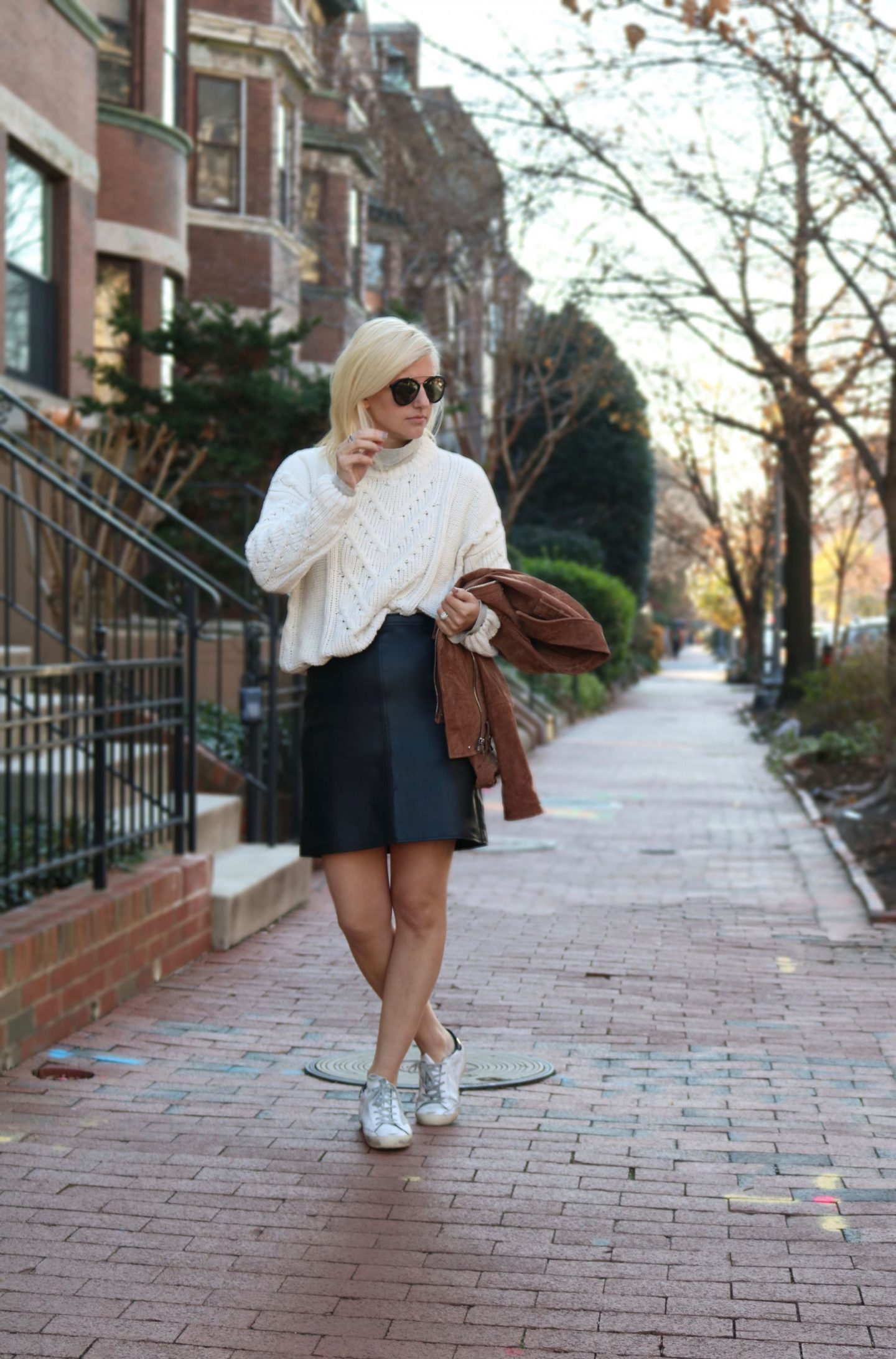 paring a leather skirt with oversized sweater, golden goose shoes, leather mini skirt
